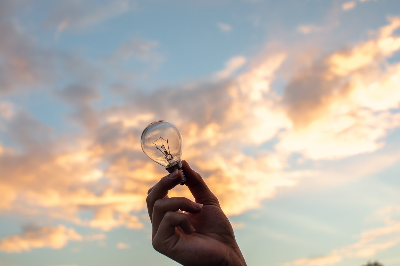 person holding clear light bulb